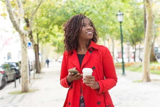 スマートフォンと紙コップを持つコンテンツ女性 無料写真