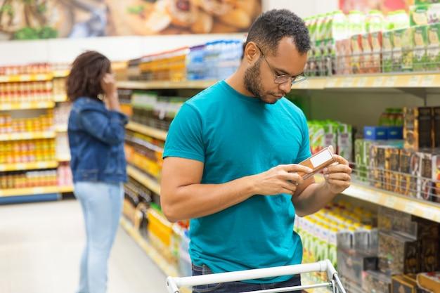 包装に関する情報を読んで焦点を当てたアフリカ系アメリカ人の男 無料写真