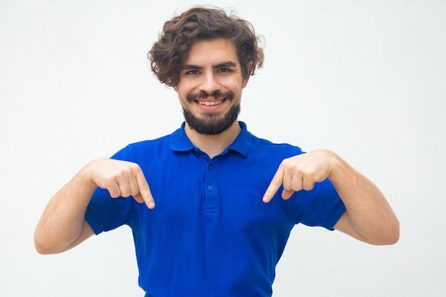 Счастливый веселый парень, указывая пальцем вниз Бесплатные Фотографии