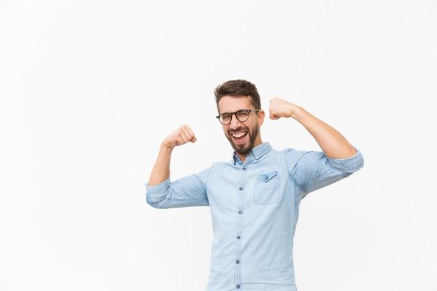 手勝者ジェスチャーを作る幸せなうれしそうな男 無料写真