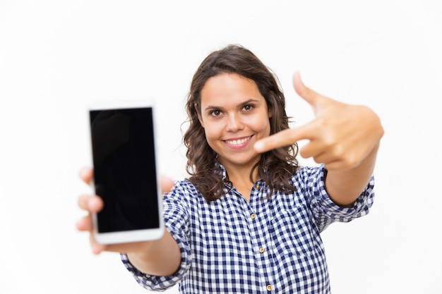 Счастливый положительный клиент, указывая пальцем на пустой экран телефона Бесплатные Фотографии