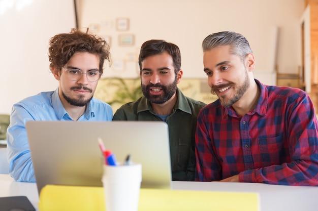 Счастливая команда стартапа наблюдает за презентацией на мониторе Бесплатные Фотографии