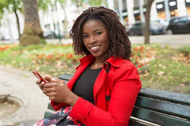 スマートフォンを笑顔で幸せな女 無料写真