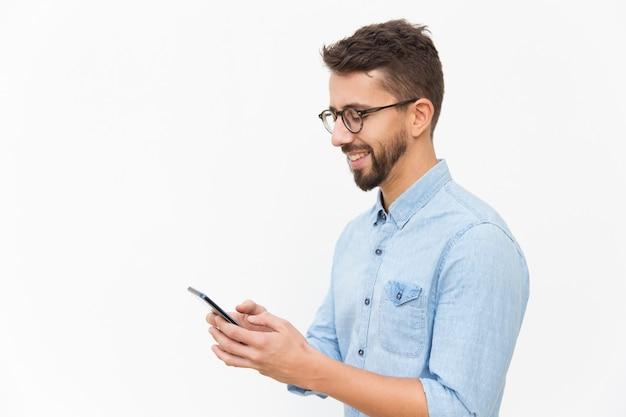 スマートフォンでうれしそうな男のテキストメッセージ 無料写真
