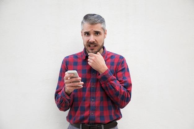 怖がっている中年の男がスマートフォンを保持 無料写真