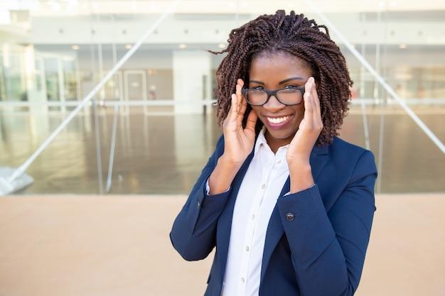 Привлекательная деловая женщина поправляет очки Бесплатные Фотографии