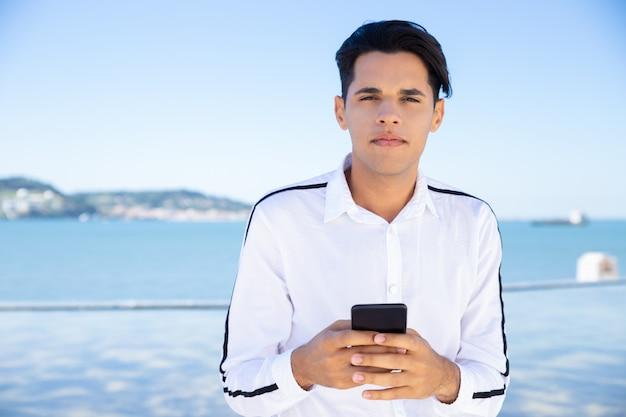 スマートフォンを使用して穏やかな若い男 無料写真