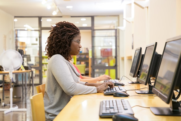 Сосредоточена женщина, набрав на клавиатуре компьютера Бесплатные Фотографии