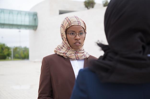 同僚と話しているイスラム教徒の女性を集中してください。 無料写真