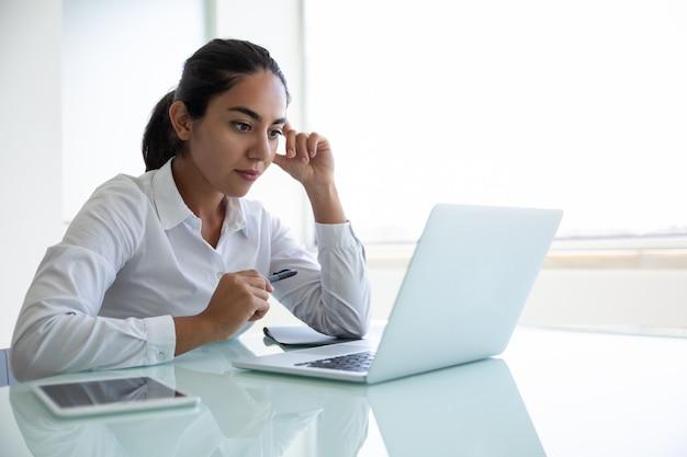 Сконцентрированная молодая коммерсантка используя компьтер-книжку в офисе Бесплатные Фотографии