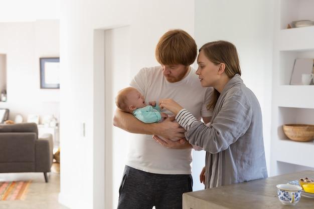 泣いている赤ちゃんを抱きしめて揺れている新しい親 無料写真