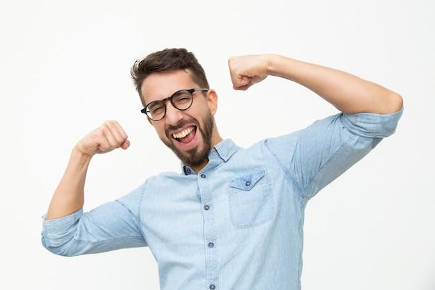 Возбужденный молодой человек показывает бицепс Бесплатные Фотографии