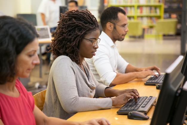 Сосредоточены афро-американских женщина, набрав на клавиатуре компьютера Бесплатные Фотографии