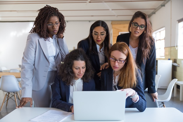Сосредоточенные деловые женщины, использующие ноутбук в офисе Бесплатные Фотографии
