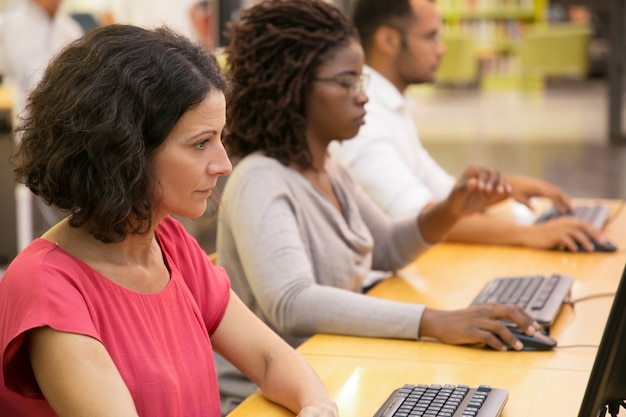 Ориентированные студенты, работающие с компьютерами в библиотеке Бесплатные Фотографии