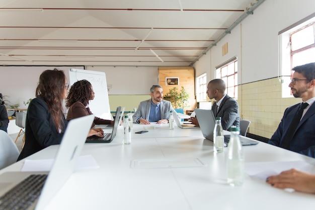 Группа занятых менеджеров во время утреннего брифинга Бесплатные Фотографии