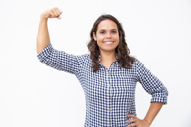 Счастливая молодая женщина показывая бицепс Бесплатные Фотографии