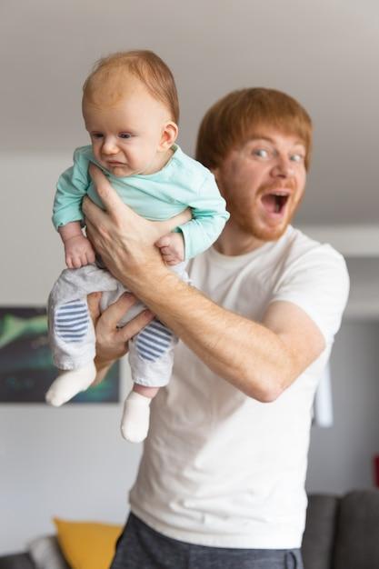 Игривый возбужденный новый отец держит сладкого ребенка Бесплатные Фотографии