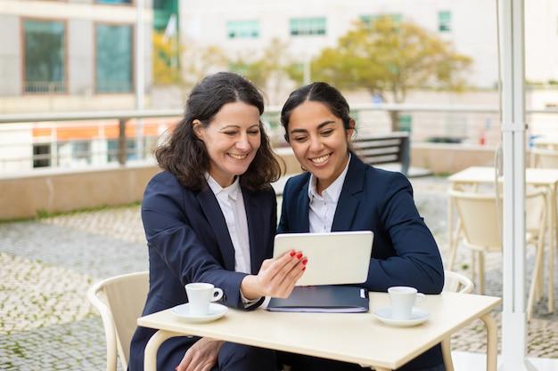 Довольные деловые женщины с планшетным пк в кафе на открытом воздухе Бесплатные Фотографии