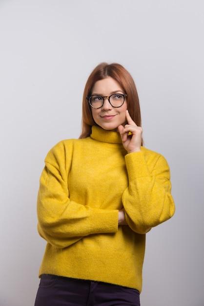 Задумчивая молодая женщина в очках смотрит вверх Бесплатные Фотографии