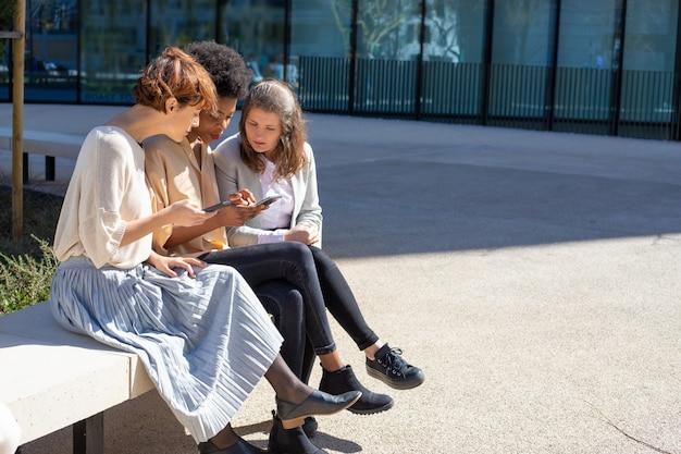 Расслабленные женщины со смартфонами разговаривают на улице Бесплатные Фотографии