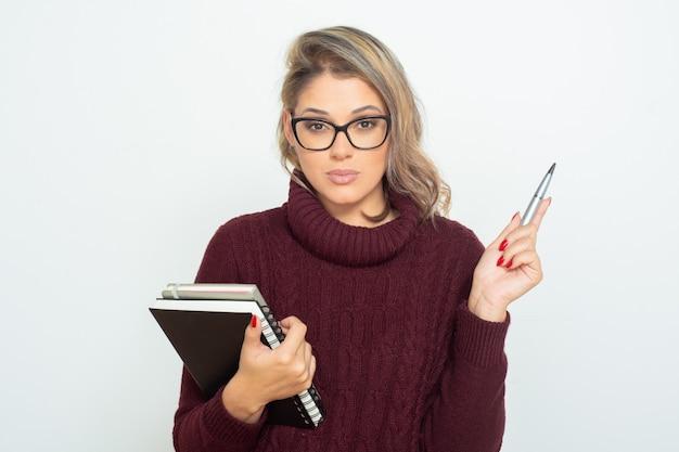 Серьезная студентка с книгами и ручкой Бесплатные Фотографии
