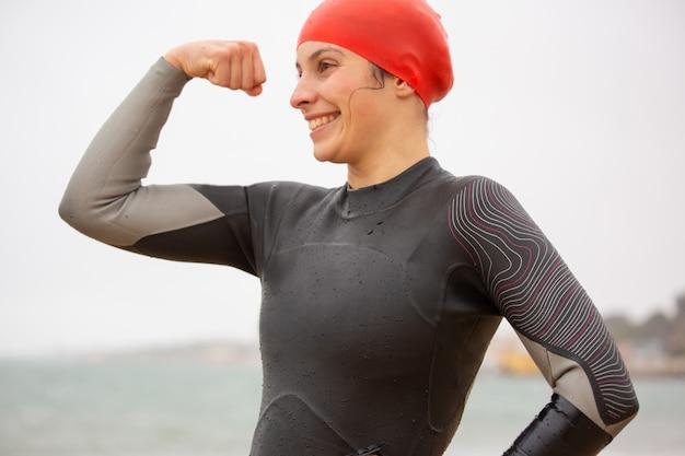 上腕二頭筋を示す笑顔の女子水泳選手 無料写真