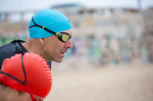 ビーチでウェットスーツの水泳選手 無料写真