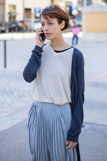 スマートフォンで話している思いやりのある若い女性 無料写真