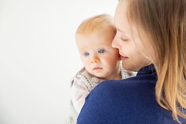 若い母親がかわいい幼児の子供を抱いて 無料写真