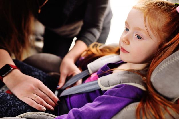 赤い髪の少女が車の中で微笑みます。 Premium写真