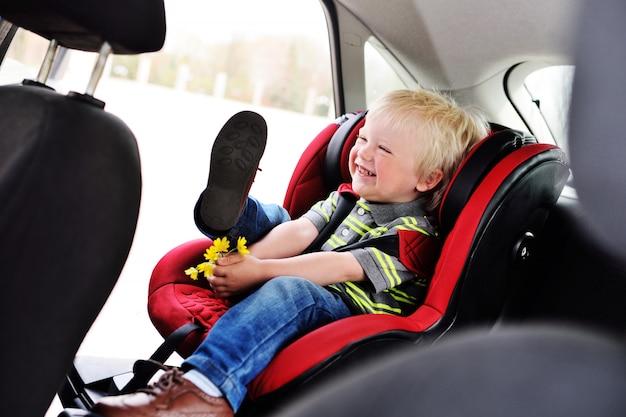 子供の車の座席にブロンドの髪を持つ少年の幼児の肖像画。 Premium写真