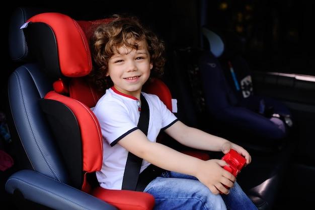 おもちゃの車の手の中で子供の車の座席に座っている巻き毛の男の子 Premium写真