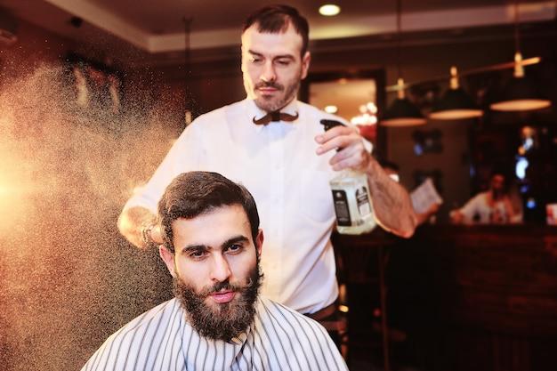 床屋は、床屋からの水で床屋の若い男性クライアントの髪に振りかけます。 Premium写真