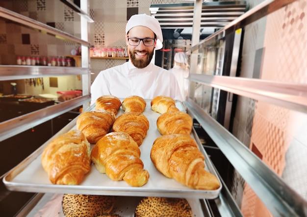 ハンサムな男性パン屋はパン屋さんと笑顔の前でフランスのクロワッサンとトレイを握ります。 Premium写真