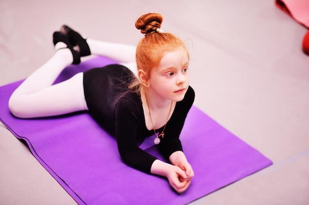 子供 - かわいい赤い髪の少女バレリーナはバレエ学校でストレッチ体操を行います Premium写真