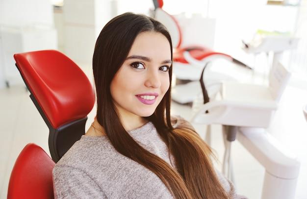 赤い歯科用椅子に笑っている美しい若い女の子 Premium写真