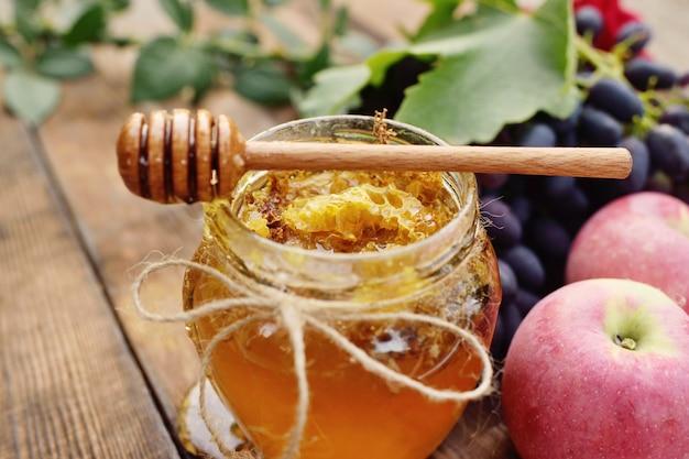 蜂蜜の美しい瓶、木のスプーンスピンドル、ブドウ、木製の背景にリンゴ Premium写真