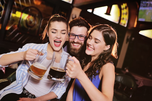 友達-ビールを飲む、話して、バーで笑顔の若い男と女 Premium写真