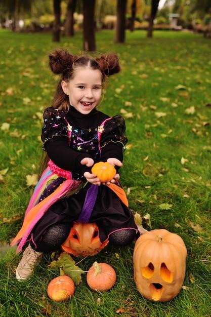 Маленькая девочка в костюме хэллоуина с тыквой празднуют хэллоуин Premium Фотографии