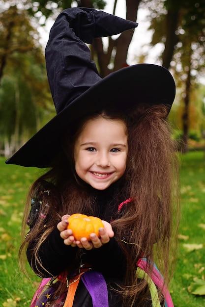 Девушка в костюме хэллоуина и в шляпе ведьмы с маленькой тыквой в руках Premium Фотографии