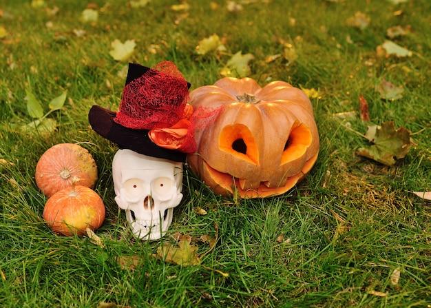 Тыква с вырезанными глазами и улыбкой и череп на траве и осенних листьях Premium Фотографии