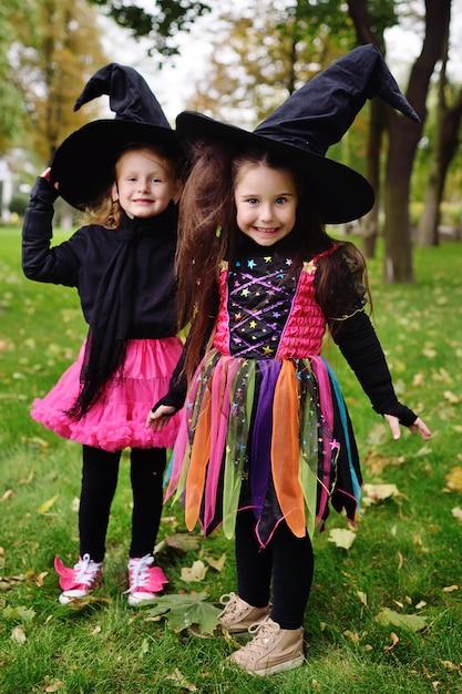 公園でハロウィーンのお祝い中にハロウィーンの衣装と大きな黒い魔女の帽子のかわいい女の子 Premium写真