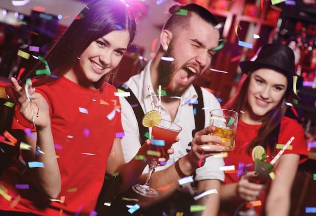 ナイトクラブのパーティーで友人のグループは、アルコール飲料とグラスをチャリンという音します。 Premium写真