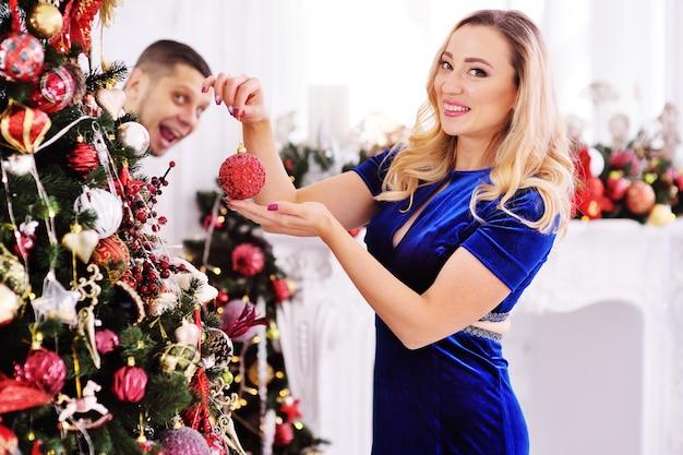 若いカップルがクリスマスツリーをドレスアップする-女性が木の上におもちゃを掛ける Premium写真