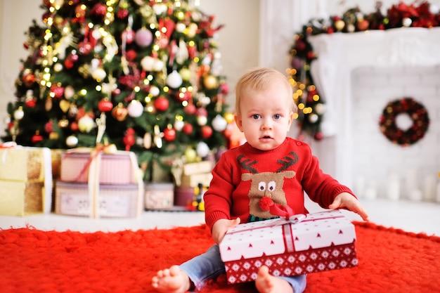 子供-サンタのトナカイの写真が付いた赤いクリスマスセーターの少年 Premium写真