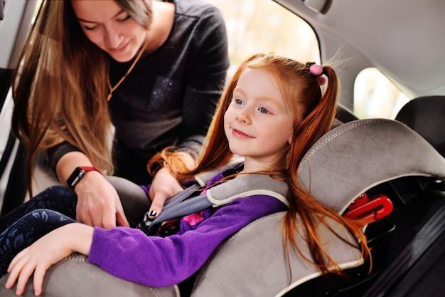 赤い髪の少女が車の中で微笑んでいます。 Premium写真