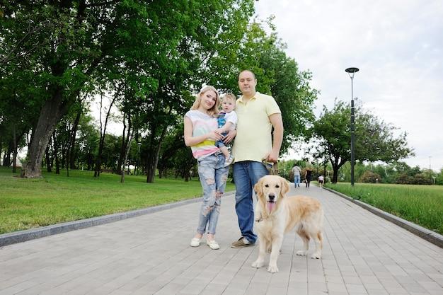 Семья с собакой золотистого ретривера в парке Premium Фотографии