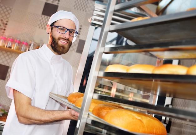 若い魅力的なベイカーは、焼きたてのペストリーが入ったトレイを、パン屋またはパン工場の表面に対して棚に置きます。 Premium写真