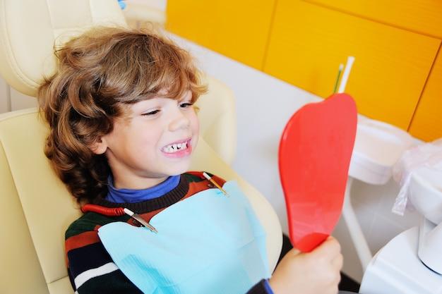 Маленький мальчик с вьющимися волосами в стоматологическом кресле открывает рот, чтобы показать, где он потерял один из зубов своего ребенка Premium Фотографии